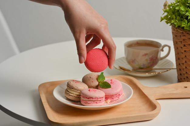 Close-up van vrouwelijke hand franse macarons plukken uit een plaat op koffietafel met kopje thee