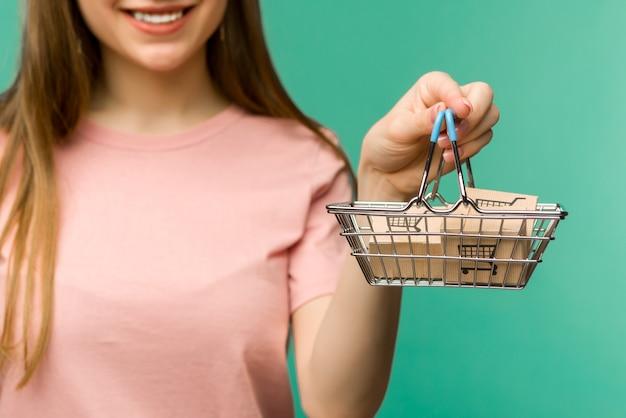 Close-up van vrouwelijke hand horizontaal houdt speelgoed metalen winkelmandje met blauw plastic handvat