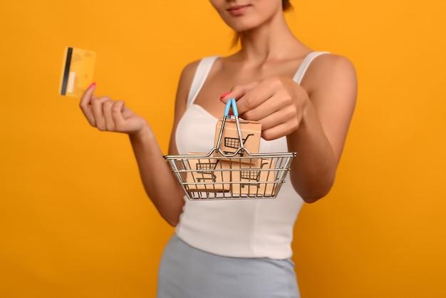 Close-up van vrouwelijke hand horizontaal houdt speelgoed metalen winkelmandje met blauwe plastic handvat en creditcard geïsoleerd op de achtergrond. beeld