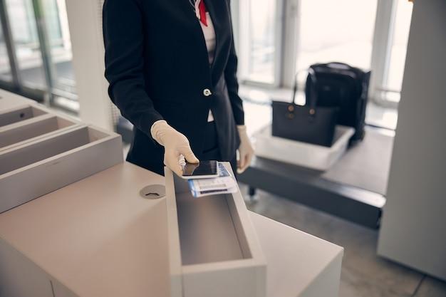 Close-up van vrouwelijke hand in steriele handschoen met instapkaart, paspoort en mobiele telefoon terwijl dame bij de incheckbalie op de luchthaven staat