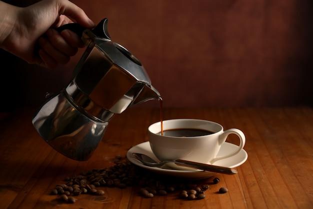 Close-up van vrouwelijke hand koffie uit koffiepot gieten in cup op houten tafel