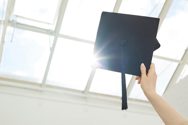 Close-up van vrouwelijke hand met afstudeerpet tegen de hemelachtergrond met zonlicht, kopieer ruimte