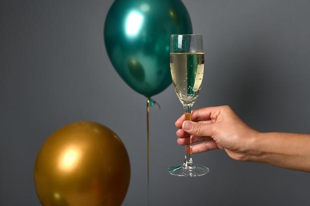 Close-up van vrouwelijke hand met een glas mousserende wijn, geïsoleerd over grijze muur achtergrond met opgeblazen mooie gouden en groene luchtballonnen. kerstmis, nieuwjaar en jubileumconcept