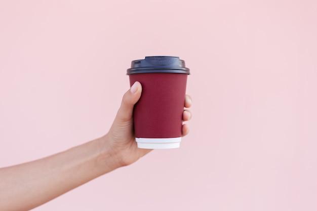 Close-up van vrouwelijke hand met een papieren koffiekopje op de achtergrond van pastel roze kleur.