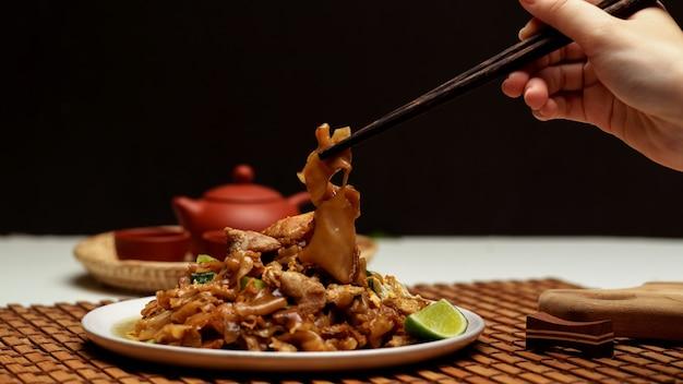 Close-up van vrouwelijke hand met eetstokje om te eten roergebakken noedel met zoete sojasaus