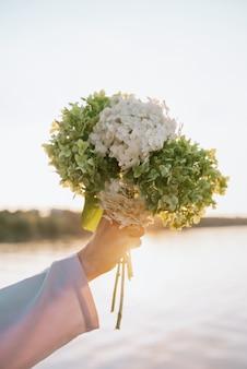 Close-up van vrouwelijke hand met hortensia bloemen in de zonsondergang buiten, ondiepe selectieve aandacht