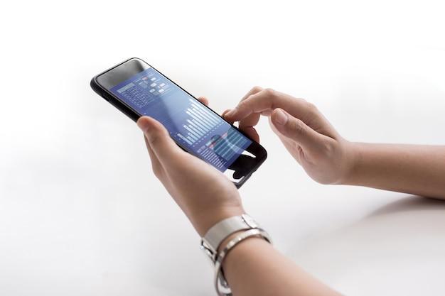 Close-up van vrouwelijke hand met smartphone met zakelijke grafiek op scherm