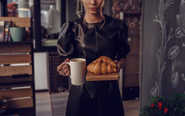Close-up van vrouwelijke hand serveren warme latte art koffie in witte kop en croissant op houten plaat in coffeeshop. cafe drinken menu warme koffie in restaurant. ontbijtmenu in de ochtendtijd.