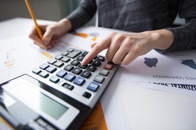 Close-up van vrouwelijke hand tellen met rekenmachine
