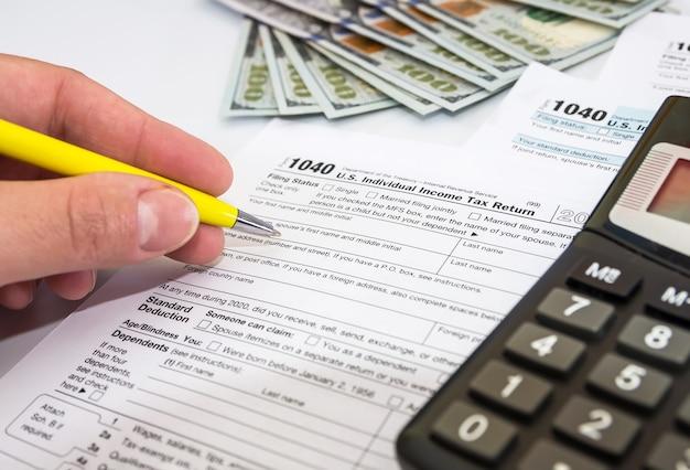 Close-up van vrouwelijke hand vult 1040 belastingformulieren op wit in