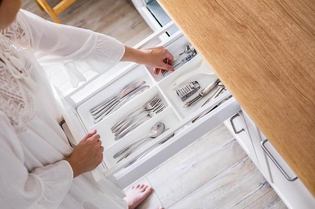 Close-up van vrouwelijke handen die bestek netjes assembleren in opbergdozen in de lade van minimalistische keuken