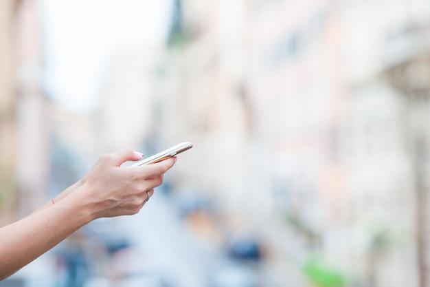 Close-up van vrouwelijke handen die cellphone in openlucht op de straat houden. vrouw die mobiele smartphone gebruikt.