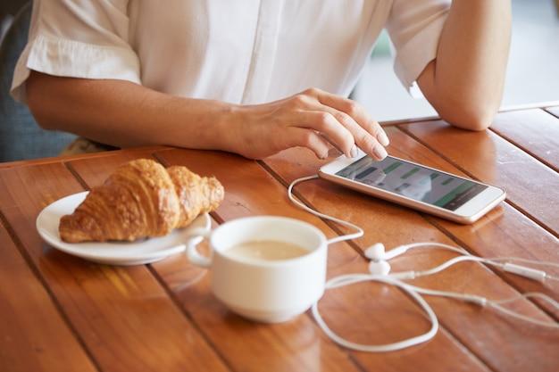Close-up van vrouwelijke handen die een bericht op smartphone texting terwijl het hebben van ochtendkoffie