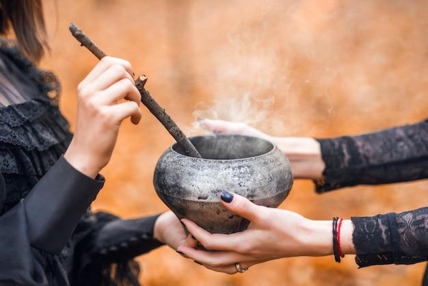 Close-up van vrouwelijke handen die een pot toverdrank houden. voorbereiden op halloween