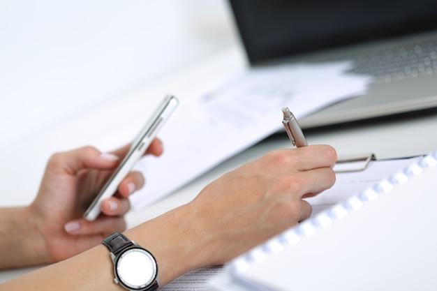 Close-up van vrouwelijke handen die met documenten op kantoor werken. vrouw die iets schrijft en naar het scherm van de mobiele telefoon kijkt