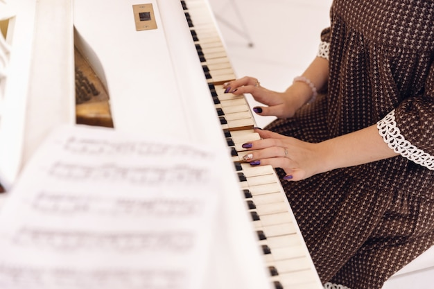 Close-up van vrouwelijke handen die pianotoetsenbord spelen