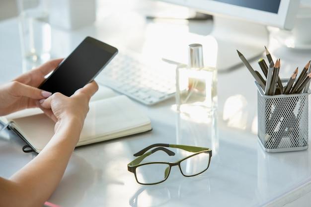 Close-up van vrouwelijke handen die telefoon met behulp van terwijl het werken aan computer op modern bureaubinnenland