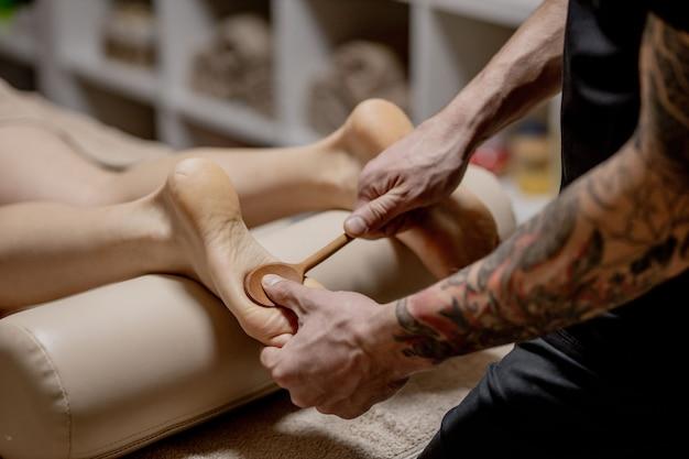 Close-up van vrouwelijke handen die voetmassage doen. vrouw genieten van reflexologie voetmassage in wellness-spa.