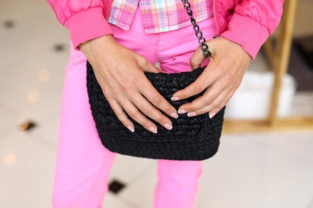 Close-up van vrouwelijke handen die zwarte handtaskoppeling houden. vrouw met stijlvolle manicure. dame in roze jeans, overhemd en jasje in winkel.