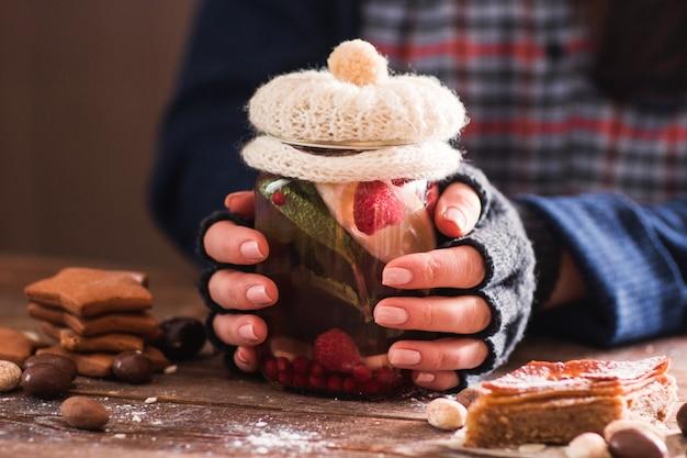 Close-up van vrouwelijke handen in handschoenen houden van glazen pot met natuurlijke drank versierd met gebreide dekking