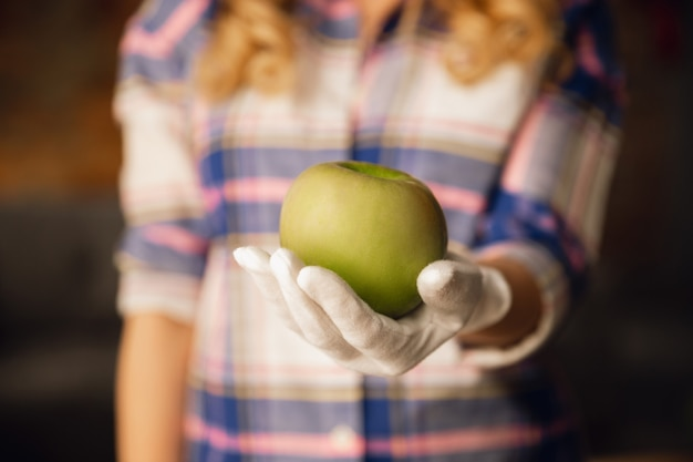 Close-up van vrouwelijke handen in handschoenen met groene appel, gezonde voeding, fruit