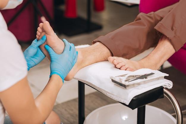 Close-up van vrouwelijke handen kneden voet terwijl vrouw werkt aan nagel bar