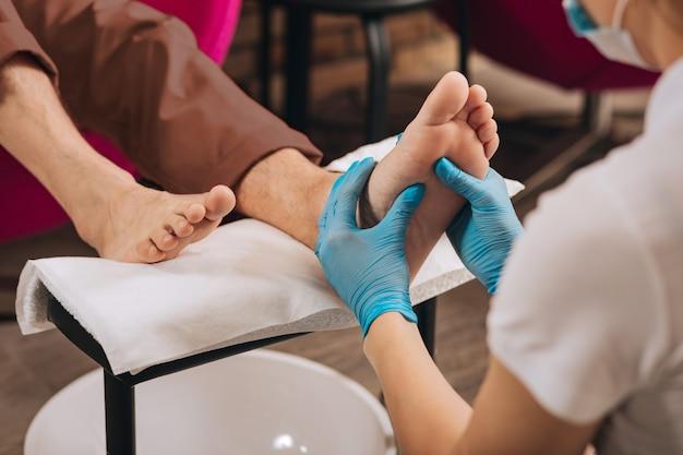 Close-up van vrouwelijke handen mannelijke voet masseren terwijl vrouw aan het werk op de nagelstaaf