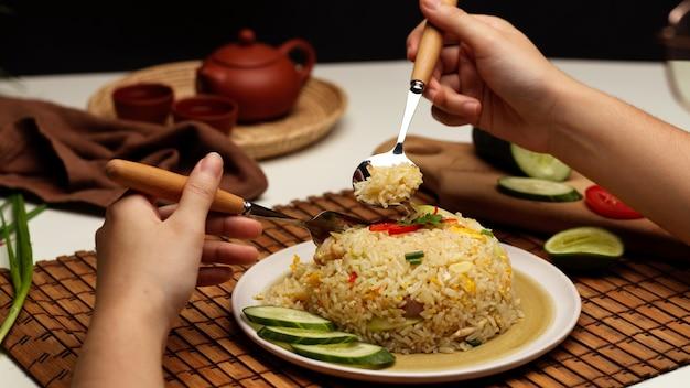 Close-up van vrouwelijke handen met bestek om thaise gebakken rijst te eten in restaurant