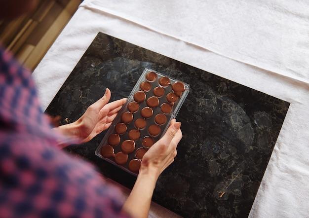 Close-up van vrouwelijke handen met chocoladevormen vol met vloeibare verwarmde chocolademassa en luxe chocolaatjes voorbereiden voor het vieren van wereldchocoladedag