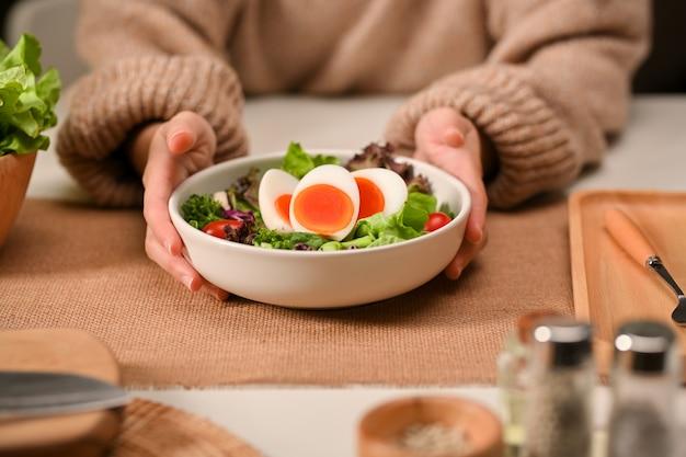 Close-up van vrouwelijke handen met een plaat van salade met gekookte eieren, sla en tomaat op de eettafel
