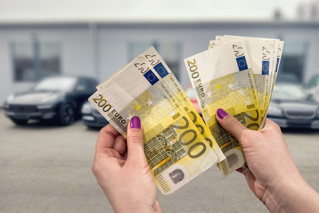 Close up van vrouwelijke handen met eurobankbiljetten op autoshow Premium Foto