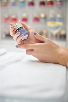Close up van vrouwelijke handen met gelakte nagels met fles gel polish aan tafel