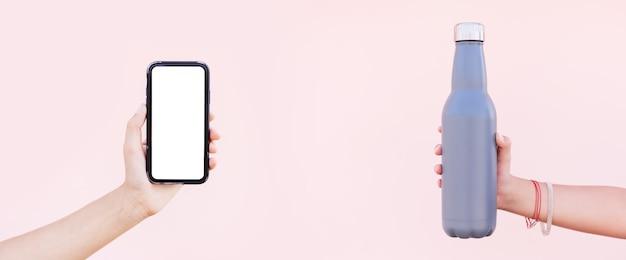 Close-up van vrouwelijke handen met herbruikbare eco thermo-waterfles en lege smartphone