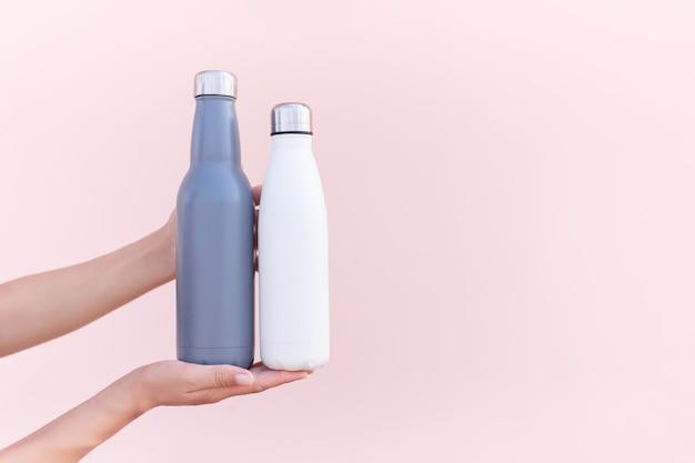 Close-up van vrouwelijke handen, met herbruikbare, stalen eco thermo-waterflessen van blauwe en witte kleuren. pastel achtergrond van roze kleur. wees plasticvrij. zero waste.