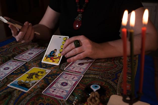 Close-up van vrouwelijke handen met tarotkaarten. waarzegster. hekserij