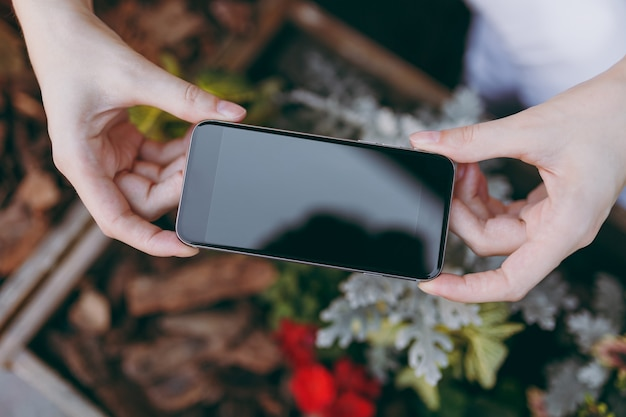 Close-up van vrouwelijke handen nemen foto op mobiele telefoon met leeg leeg scherm