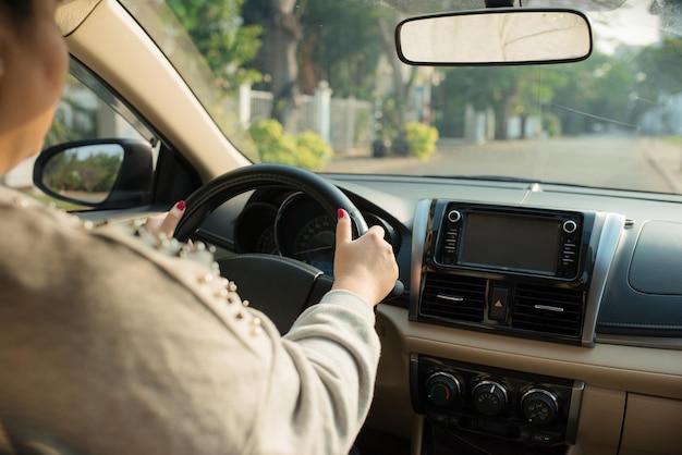 Close up van vrouwelijke handen op het stuur. reiziger meisje op autorit, kijkend naar de weg. uitzicht over schouder