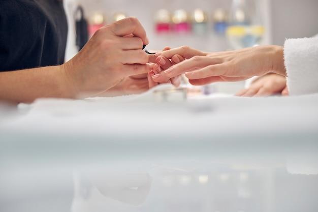 Close up van vrouwelijke handen op tafel bedekt met gellak door professional in salon