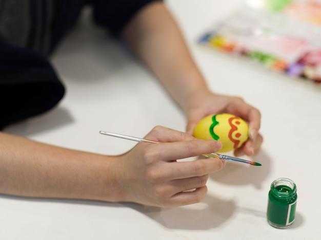 Close-up van vrouwelijke handen schilderen op eieren ter voorbereiding op paasfestival op ambachtelijke tafel