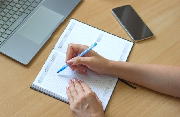 Close-up van vrouwelijke handen schrijven in notitieboekje op een houten tafel, smartphone en laptop liggen ernaast