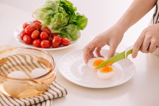 Close up van vrouwelijke handen snijden gekookt ei voor zijn ontbijt en gemengde groenten op witte houten achtergrond