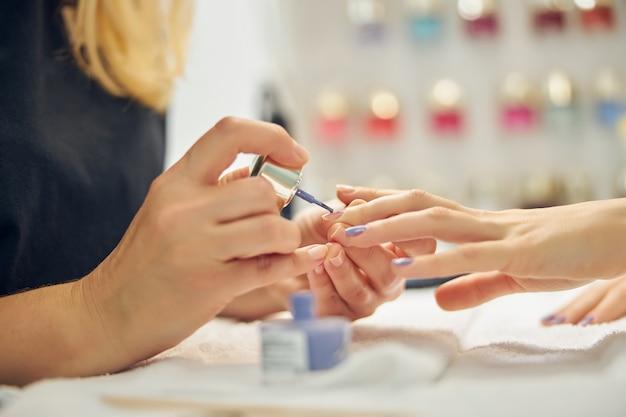 Close-up van vrouwelijke handen terwijl schoonheidsspecialiste ze schildert met blauwe gellak gel