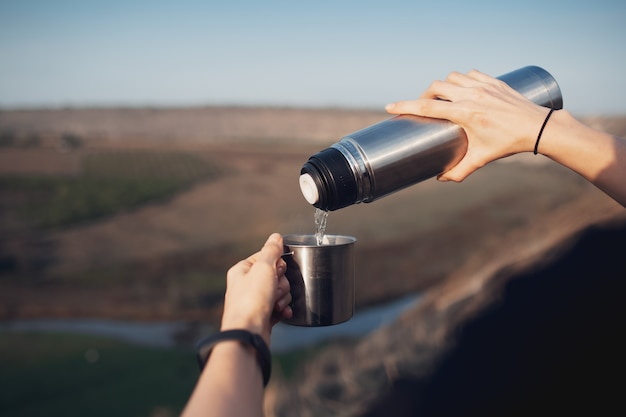 Close-up van vrouwelijke handen, thee gieten in de stalen beker van thermoskan, op buiten achtergrond. reis concept.