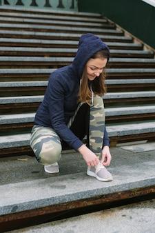 Close-up van vrouwelijke jogger bindende schoenveter op bleker
