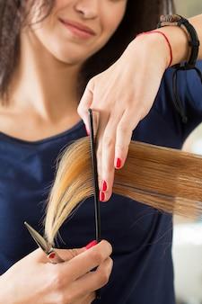 Close-up van vrouwelijke kapper handen haren tips knippen. herstel van keratine, gezond haar, nieuwste haarmodetrends, veranderende kapselstijl, kortere gespleten punten, instrumentwinkelconcept