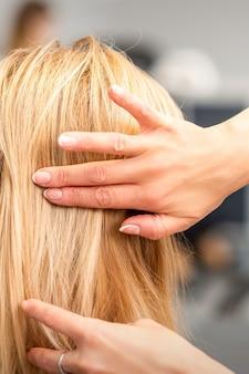 Close up van vrouwelijke kapper styling blonde haren van een jonge vrouw in een schoonheidssalon