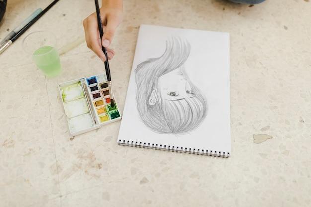 Close-up van vrouwelijke kunstenaar die het gezichtsschets van het wijfje met waterverf schildert