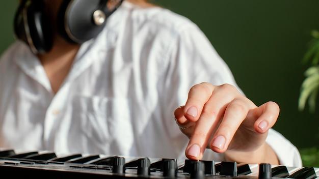 Close-up van vrouwelijke muzikant met pianotoetsenbord en koptelefoon binnenshuis