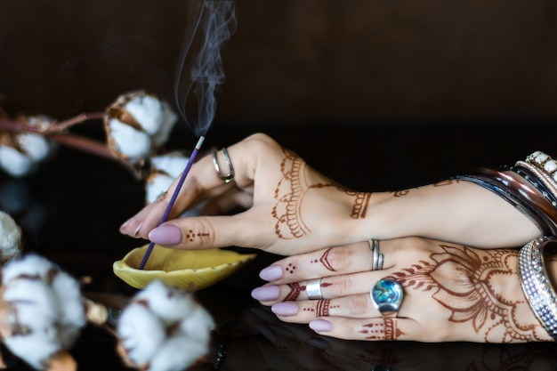 Close-up van vrouwelijke polsen beschilderd met henna traditionele indiase oosterse mehndi ornamenten. handen gekleed in armbanden en ringen zetten aromatische stok in stand. tak met katoenen bloemen op achtergrond.