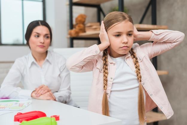 Close-up van vrouwelijke psycholoog die geërgerd meisje bekijken die haar oren behandelen met twee handen